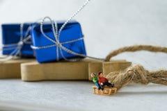 Glückliche Miniaturkinder, die den Pferdeschlitten mit dem Präsentkarton reiten Stockfoto