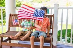 Glückliche Mischrasse chinesisch und kaukasische Brüder, die mit amerikanischen Flaggen spielen stockfotos