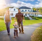Glückliche Mischrasse-Familie, die vor schönem kundenspezifischem Haus geht stockfotos