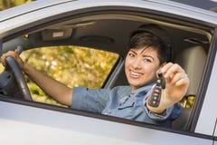 Glückliche Mischrasse-Frau im Auto, das Schlüssel hält Stockfotografie