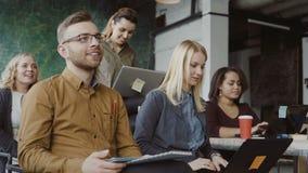 Glückliche Mischrassegruppe von personen im Dachbodenbüro Mann und Frau mit Laptop, Tablette an hörendem Sprecher des Geschäftsvo stock video footage