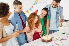 Glückliche Mitarbeiter mit Kuchen an der Bürogeburtstagsfeier lizenzfreie stockbilder