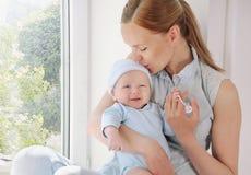 Glückliche mitfühlende Mutter, die ihr nettes neugeborenes Baby küsst Lizenzfreies Stockbild