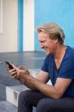 Glückliche Mitte alterte den Mann, der auf Schritten unter Verwendung des Handys sitzt Lizenzfreie Stockfotos