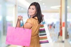 Glückliche Mitte gealterte Asiatin, die Einkaufstaschen hält Stockfotos