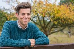 Glückliche Mitte gealterter Mann außerhalb des Lehnens auf einem Zaun Lizenzfreie Stockfotos