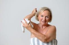 Glückliche Mittelalter-Frau, die ihren Arm mit Tuch trocknet Lizenzfreies Stockbild