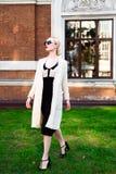 Glückliche Mode-blonde europäische elegante Frau mit den roten Lippen und weißen der Haut, die am alten Gebäude des roten Backste Lizenzfreies Stockbild