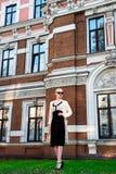 Glückliche Mode-blonde europäische elegante Frau mit den roten Lippen und weißen der Haut, die am alten Gebäude des roten Backste Stockfotografie
