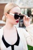 Glückliche Mode-blonde europäische elegante Frau mit den roten Lippen und weißen der Haut, die am alten Gebäude des roten Backste Stockbild
