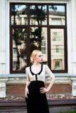 Glückliche Mode-blonde europäische elegante Frau mit den roten Lippen und weißen der Haut, die am alten Gebäude des roten Backste Stockfoto