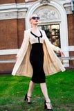 Glückliche Mode-blonde europäische elegante Frau mit den roten Lippen und weißen der Haut, die am alten Gebäude des roten Backste Lizenzfreies Stockfoto