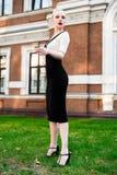 Glückliche Mode-blonde europäische elegante Frau mit den roten Lippen und weißen der Haut, die am alten Gebäude des roten Backste Stockfotos