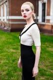 Glückliche Mode-blonde europäische elegante Frau mit den roten Lippen und weißen der Haut, die am alten Gebäude des roten Backste Lizenzfreie Stockfotos