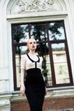 Glückliche Mode-blonde europäische elegante Frau mit den roten Lippen und weißen der Haut, die am alten Gebäude des roten Backste Lizenzfreie Stockfotografie