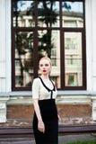 Glückliche Mode-blonde europäische elegante Frau mit den roten Lippen und weißen der Haut, die am alten Gebäude des roten Backste Lizenzfreie Stockbilder