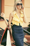 Glückliche Modefrau mit Einkaufstaschen im Einkaufszentrum sprechend am Handy Stockfotografie