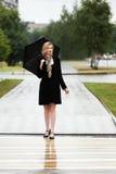 Glückliche Modefrau mit Regenschirm gehend auf eine Stadtstraße Stockbilder