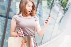 Glückliche Modefrau mit Tasche unter Verwendung des Handys, Einkaufszentrum Lizenzfreies Stockfoto