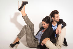 Glückliche Modepaare, die zusammen auf dem Boden sitzen Stockfotografie