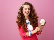 Glückliche moderne Frau lokalisiert auf rosa darstellendem Bauernhof organischer Jogurt Lizenzfreies Stockbild