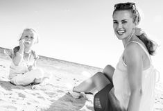 Glückliche moderne Mutter und Kind auf Schlagblasen der Seeküste lizenzfreies stockbild