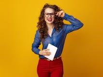 Glückliche modische Frau gegen gelben Hintergrund mit Tablet-PC Lizenzfreie Stockbilder