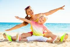 Glückliche modische Mutter und Tochter auf der Seeküste, die Spaßzeit hat stockfoto