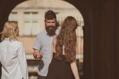 Glückliche Momente Bärtiger Mann und hübsche Frauen, die auf Straße lächeln Bindungen der Freundschaft Freunddatierungsfreundinne lizenzfreies stockbild