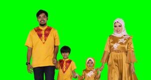 Glückliche moslemische Familie, die in das Studio geht