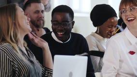 Glückliche multiethnische Geschäftsleute sitzen am Seminar, am Lachen und am Lächeln bei der modernen Bürositzung E stock video footage