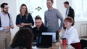 Glückliche multiethnische lächelnde Gruppe, die im Dachbodenbüro, lösend mit mittlerem gealtertem Chef bei der Konferenz zusammen stock video footage