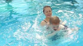 Glückliche Mutter der Nahaufnahme unterrichtet ihren Sohn, im Pool zu schwimmen Klappstuhl auf Strand in Brighton stock video