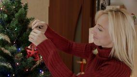 Glückliche Mutter, die Baum des neuen Jahres mit rotem Stern decotating ist stock video