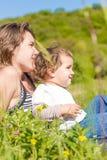 Glückliche Mutter, die draußen mit ihrem Kindermädchen spielt Stockfotos