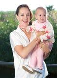 Glückliche Mutter, die draußen schönes Baby hält Stockbild