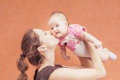 Glückliche Mutter, die ihr Baby am Wandhintergrund küsst Lizenzfreies Stockbild
