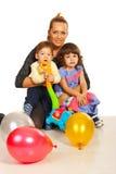 Glückliche Mutter, die ihre Kinder umfasst Stockfotos
