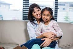 Glückliche Mutter, die ihre Tochter umfaßt Stockfoto