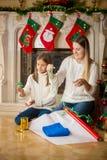 Glückliche Mutter, die ihrer Tochter beibringt, wie man Weihnachtsgeschenk einwickelt Stockbilder