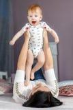 Glückliche Mutter, die mit dem Baby zu Hause liegt auf Bett spielt Stockbilder