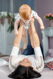 Glückliche Mutter, die mit dem Baby zu Hause liegt auf Bett spielt Stockbild