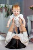 Glückliche Mutter, die mit dem Baby zu Hause liegt auf Bett spielt Lizenzfreies Stockbild