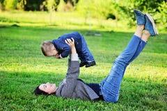 Glückliche Mutter, die mit ihrem Sohn im Park spielt Lizenzfreies Stockfoto