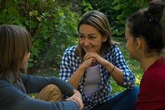 Glückliche Mutter, die mit ihren Kindern im Park spricht lizenzfreies stockfoto