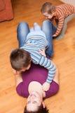 Glückliche Mutter, die mit Kindern auf dem Boden spielt Stockbilder