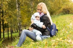 Glückliche Mutter, die mit nettem Jahrkleinkind im Herbstpark spielt Lizenzfreies Stockfoto