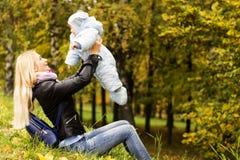 Glückliche Mutter, die mit nettem Jahrkleinkind im Herbstpark spielt Stockfoto
