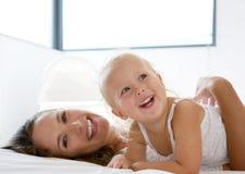 Glückliche Mutter, die mit nettem kleinem Mädchen spielt Stockbilder