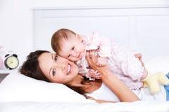 Glückliche Mutter, die mit Schätzchen liegt Lizenzfreie Stockfotografie